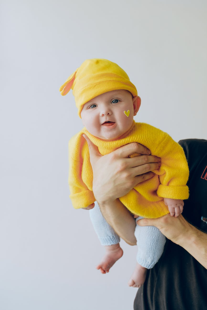 crop parent holding smiling baby in arms against gray wall in room