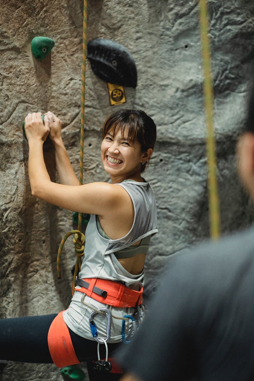 joyful young ethnic female boulderer having fun while climbing wall in gym