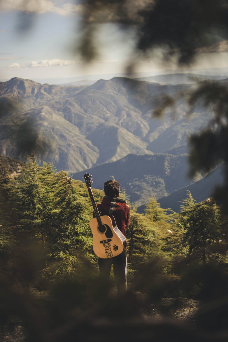 person with acoustic guitar standing in green field near mountain