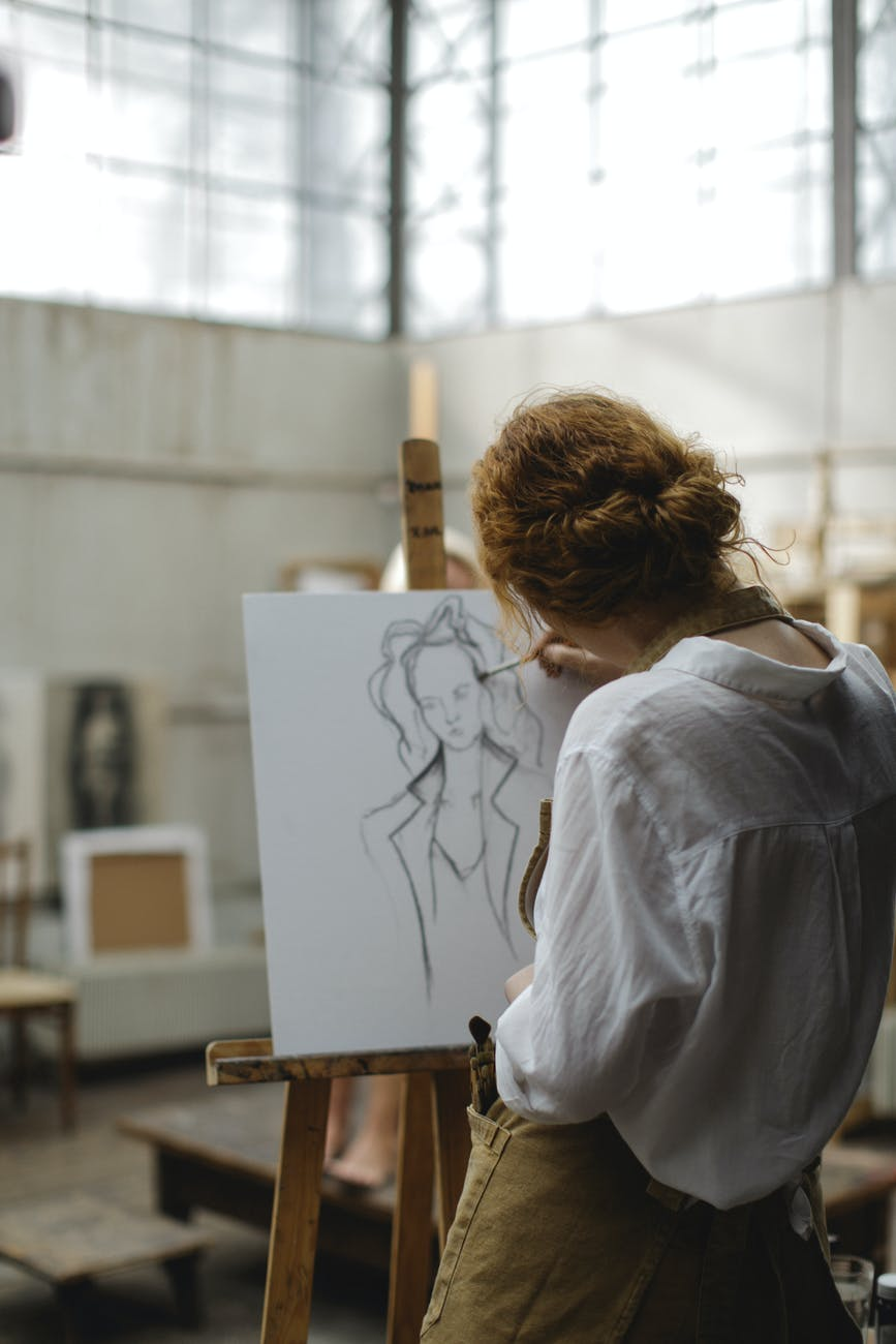 woman in white long sleeves sketching a woman