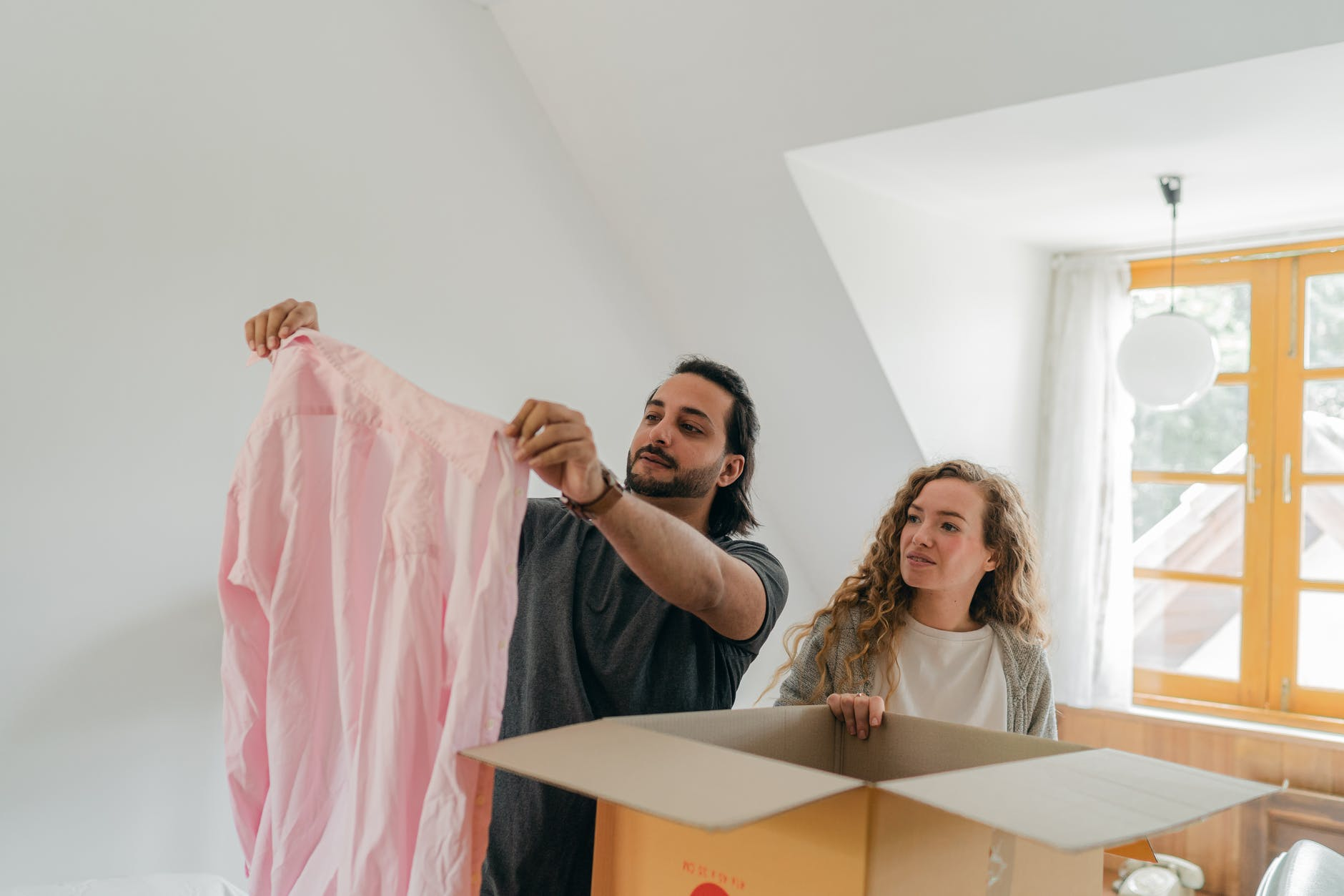 happy couple unpacking carton boxes in new apartment