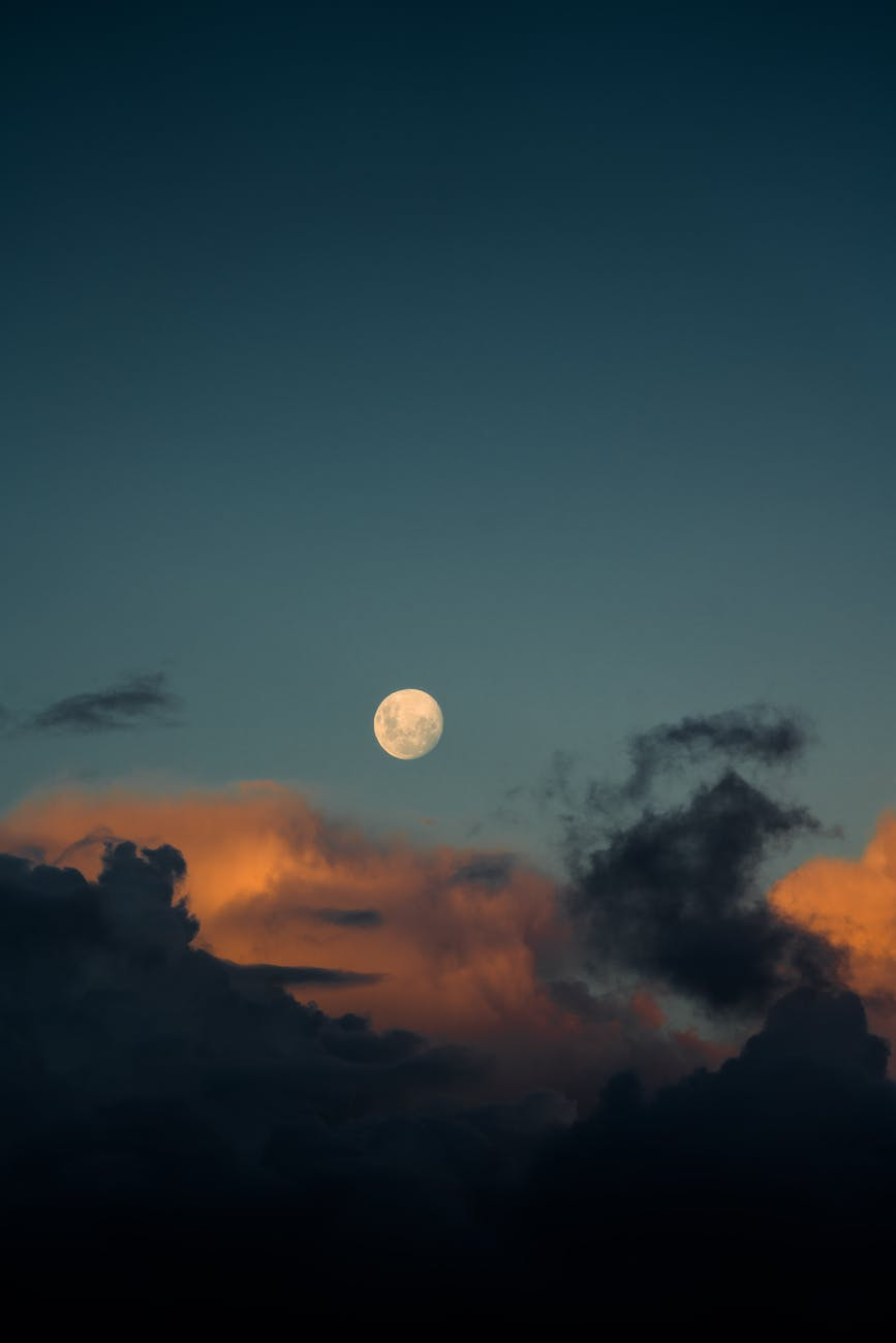 moon among fluffy clouds in dusky evening
